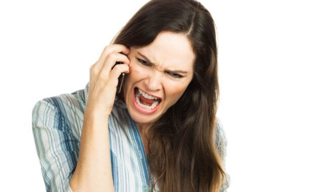 An angry and very frustrated business woman yelling on the phone. Isolated over white.
